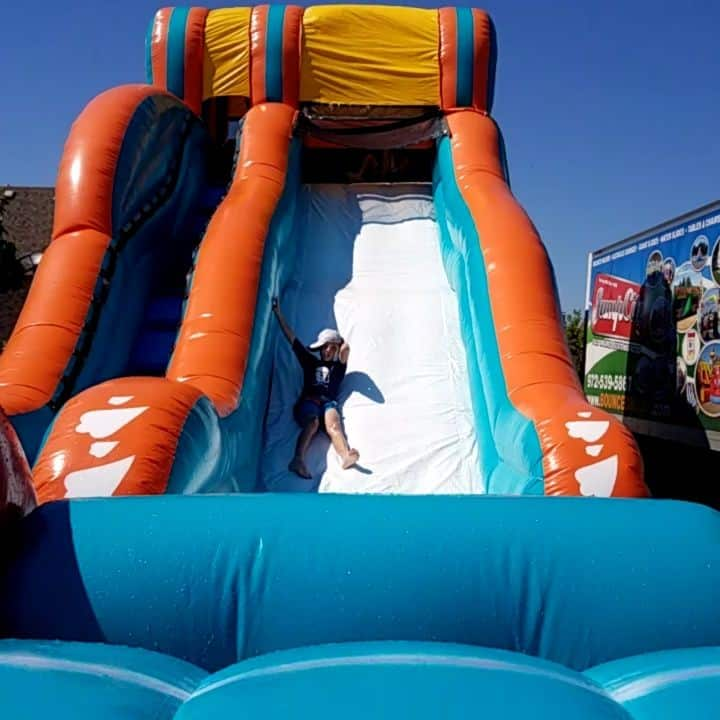 kid sliding down big kahuna inflatable water slide rental front view