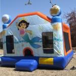 Dora the Exploerer Mermaid bounce house jump house rental on grass in sunlight