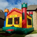 Medieval Air Castle bounce house jump house in front of a house on grass