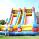 colorful primary colored double two slide combination inflatable rental on grass