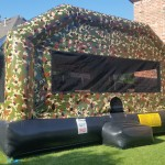 big camouflage bounce house on grass in a backyard