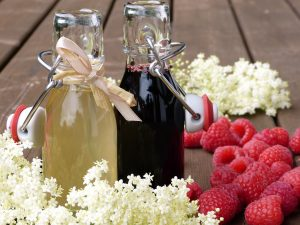two-homemade-glass-bottle-syrups-raspberries-white-flowers