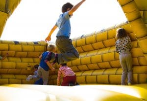 four-kids-playing-in-yellow-bounce-house