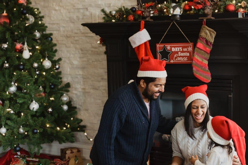 family around christmas tree wearing santa hats