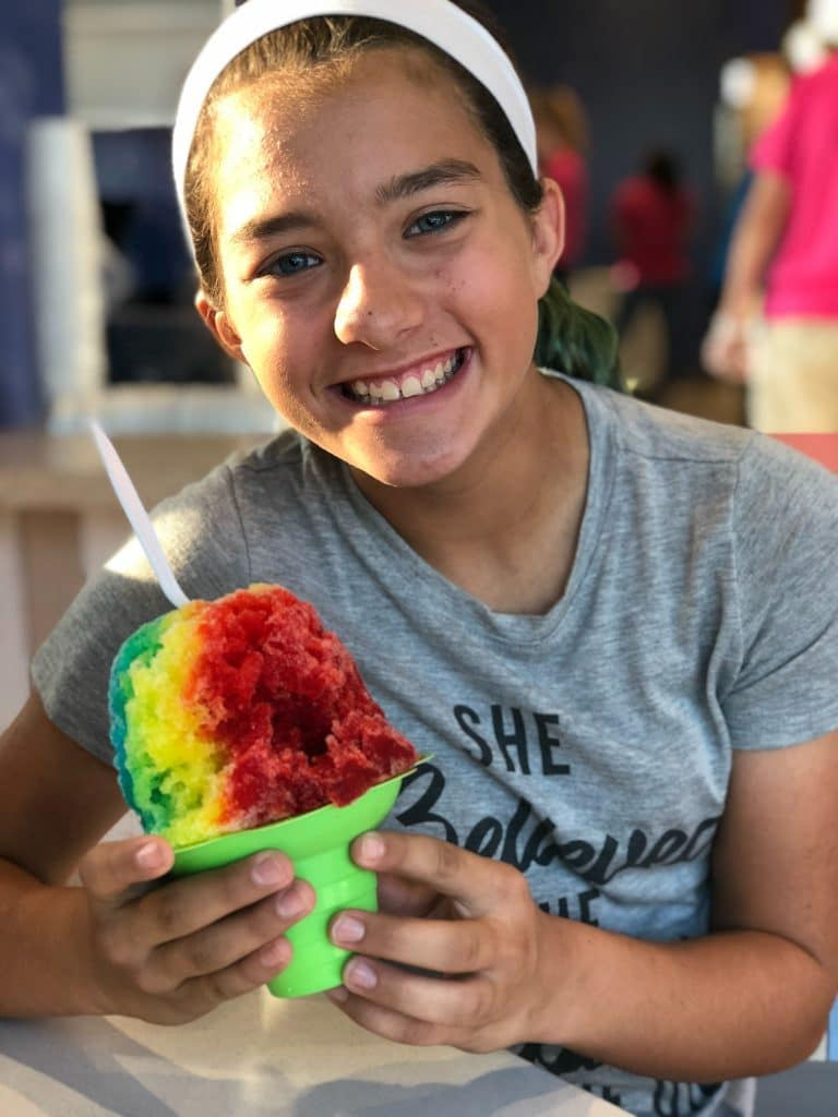girl sitting on chair holding sno cone