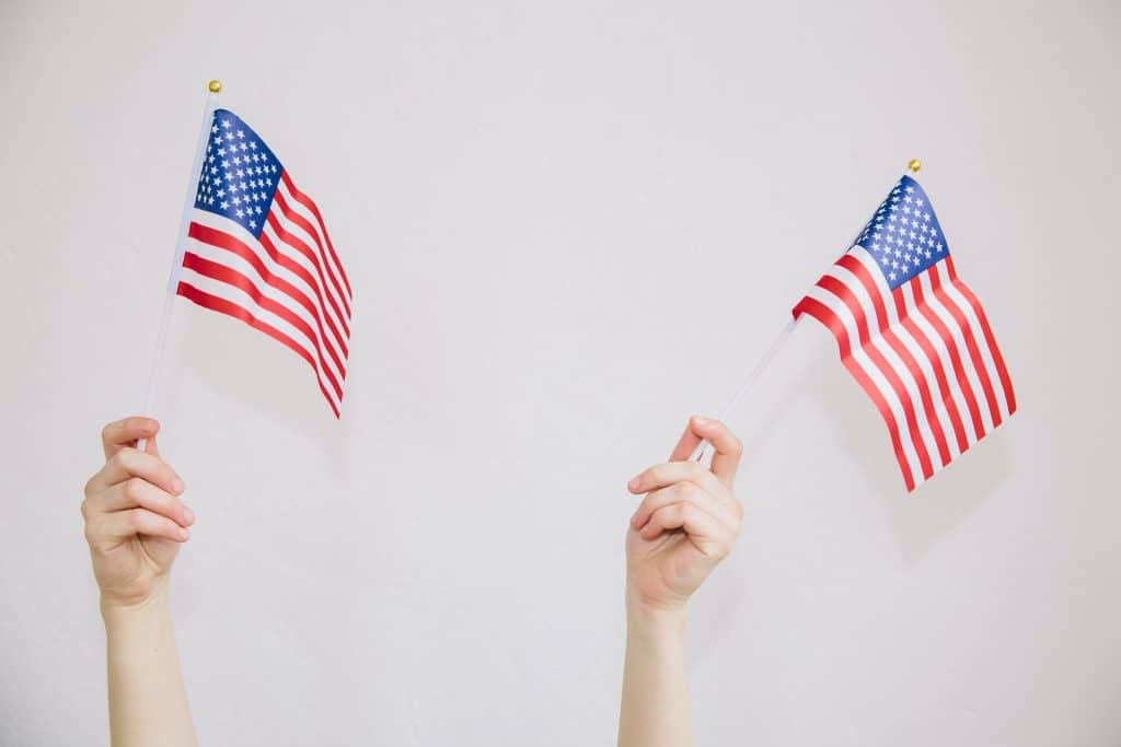 two hands waving mini American flags