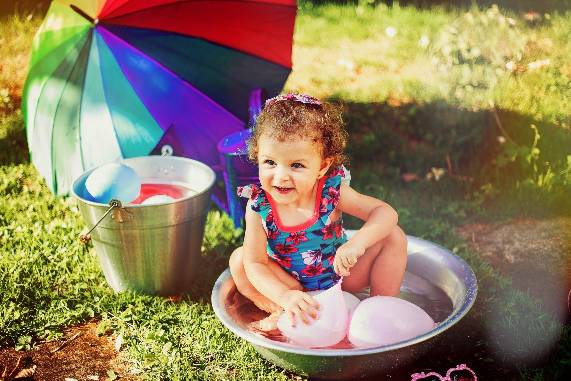 little girl sitting in small pool with water balloons