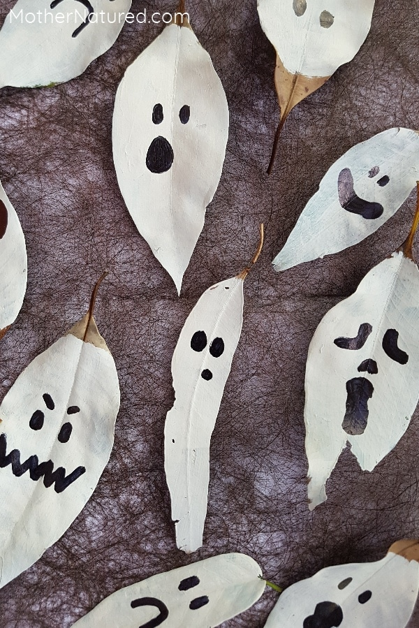 leaves painted white like ghost with faces drawn on in permanent marker