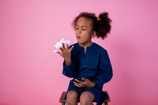 little girl sitting on a stool eating cotton candy