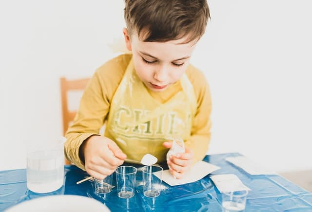 little boy sitting at a table doing a science experiment with salt and tubes