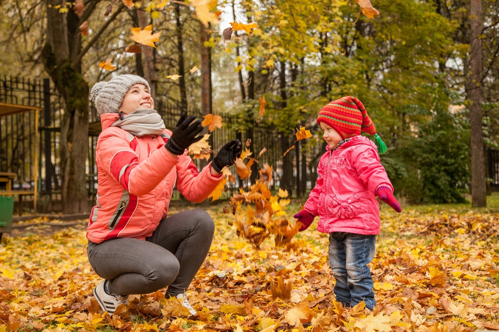 mom and little girl play in the fall leaves