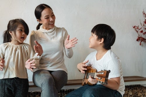 mom, daughter, and son, sitting together singing and smiling