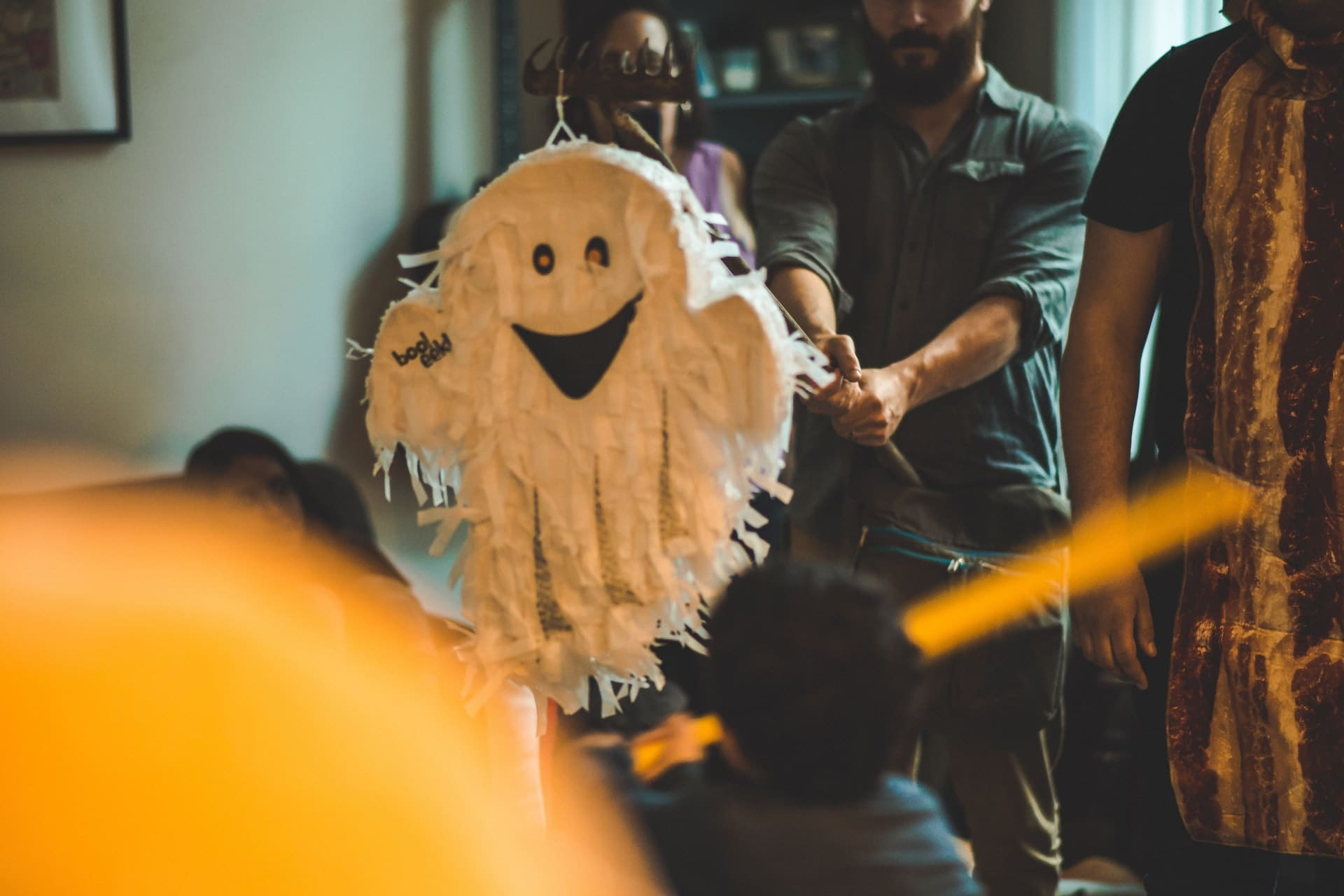 family inside home hitting halloween ghost pinata