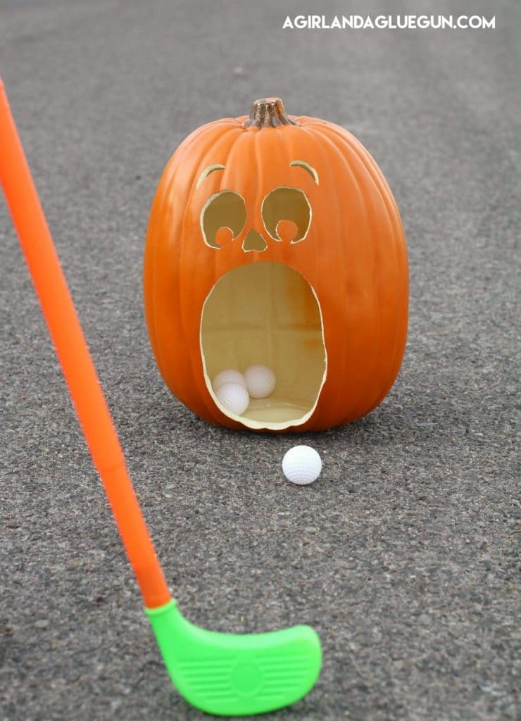 pumkin carved with open mouth and person golfing golf balls into the pumpkins mouth