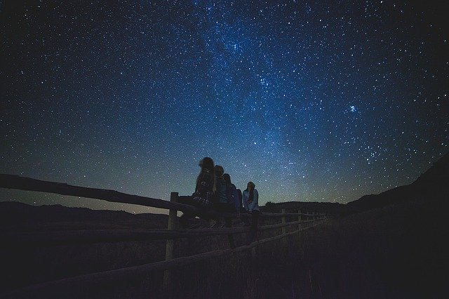 poeple sitting on a fence looking up at the stars stargazing