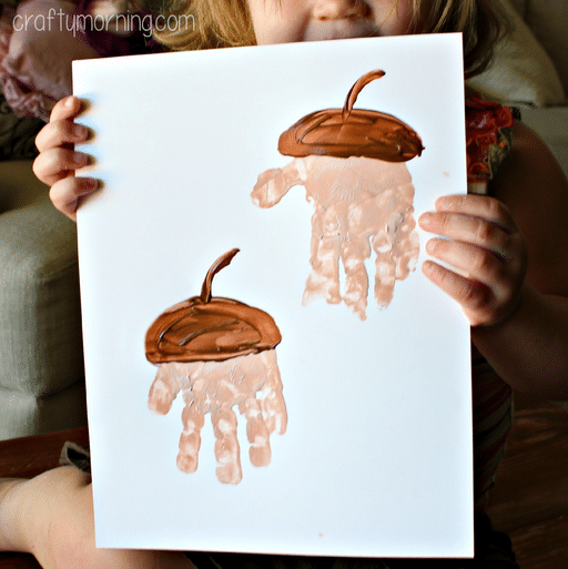 handprint paint on paper resembling an acorn with small child holding up the paper