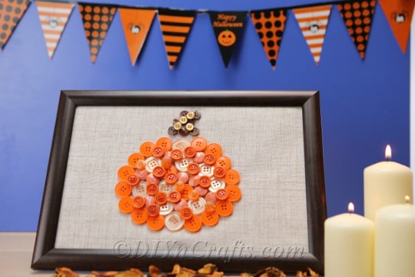 pumpkin wall art shaped from orange colored buttons