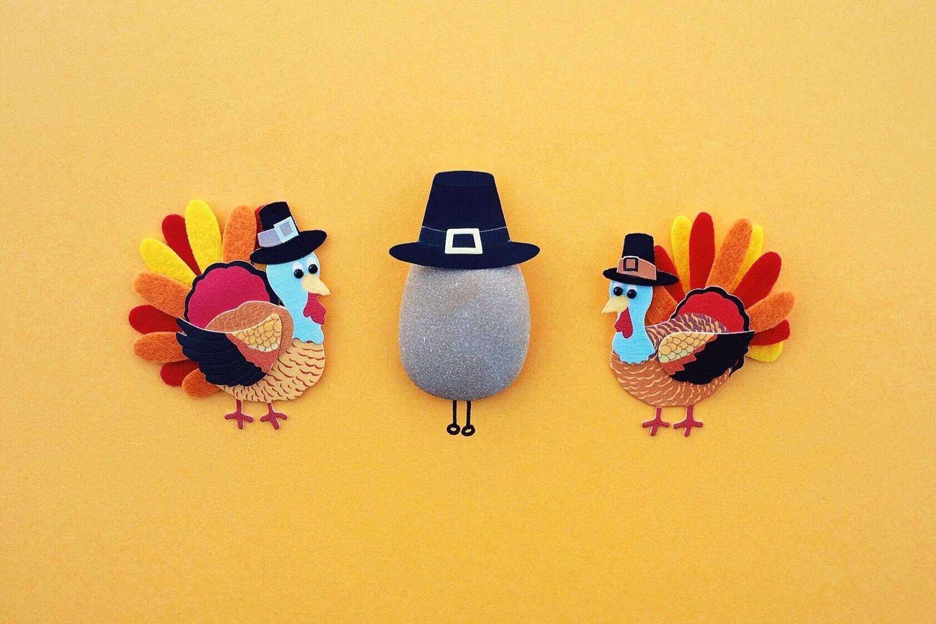 two Turkey crafts in pilgtim hats on either side of a rock also with a pilgrim hat