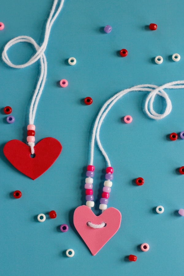 two homemade necklaces on yarn one pink herat one red heart with red white and pink beads