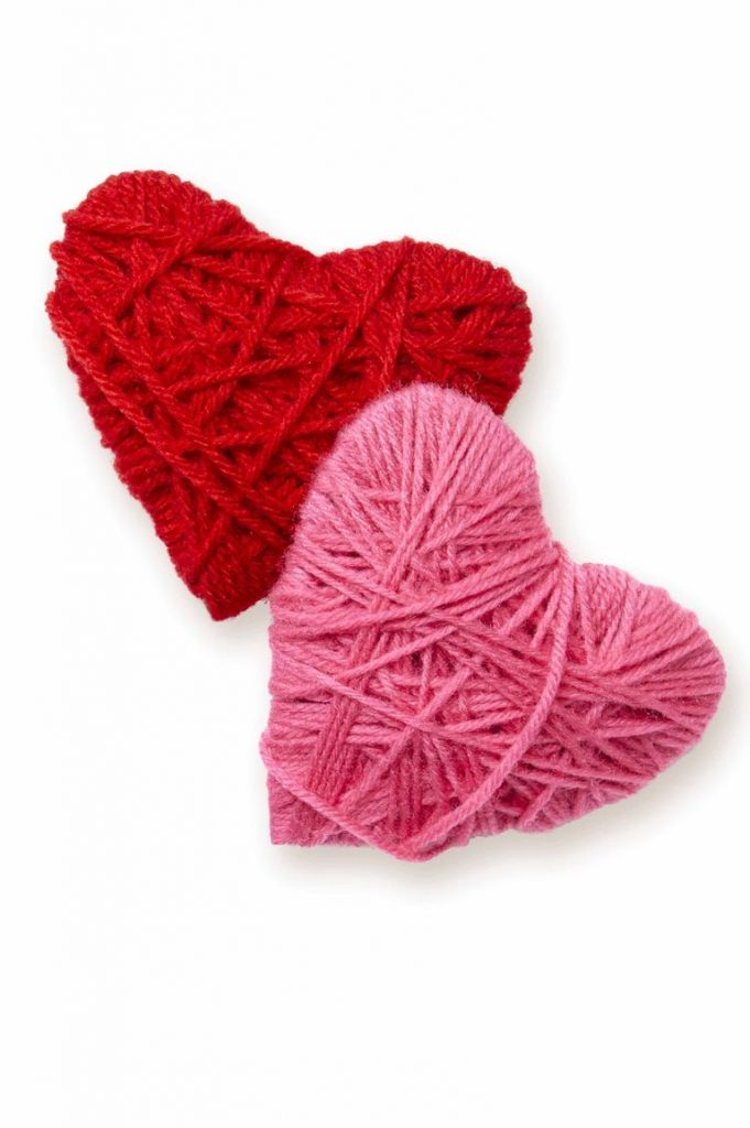 two yarn wrapped hearts one in red yarn and one in pink yarn