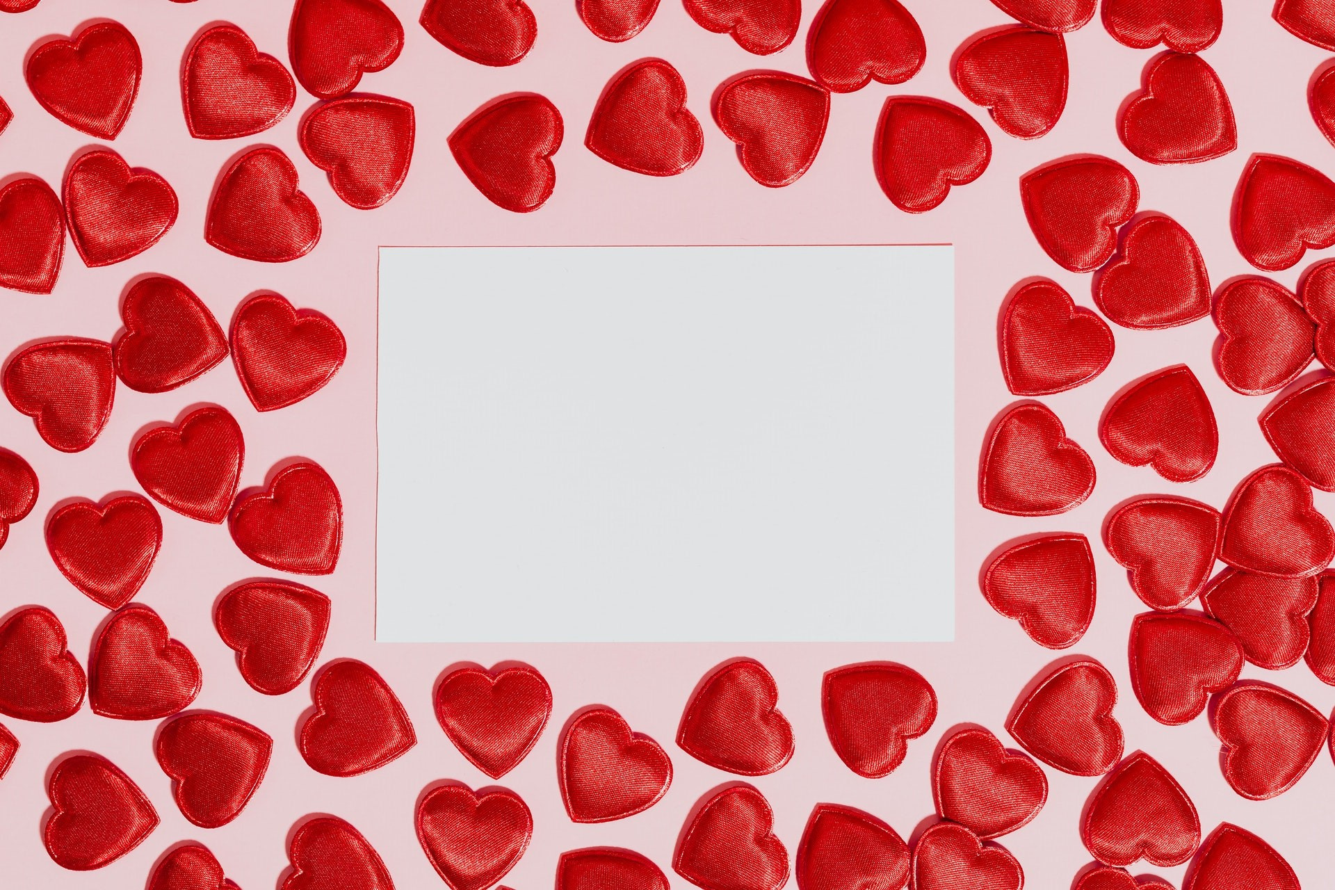white blank piece of paper surrounded by re hearts on a pink background