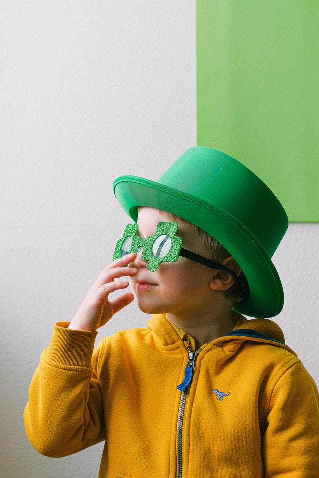 little boy in green four leaf clover glasses and green hat