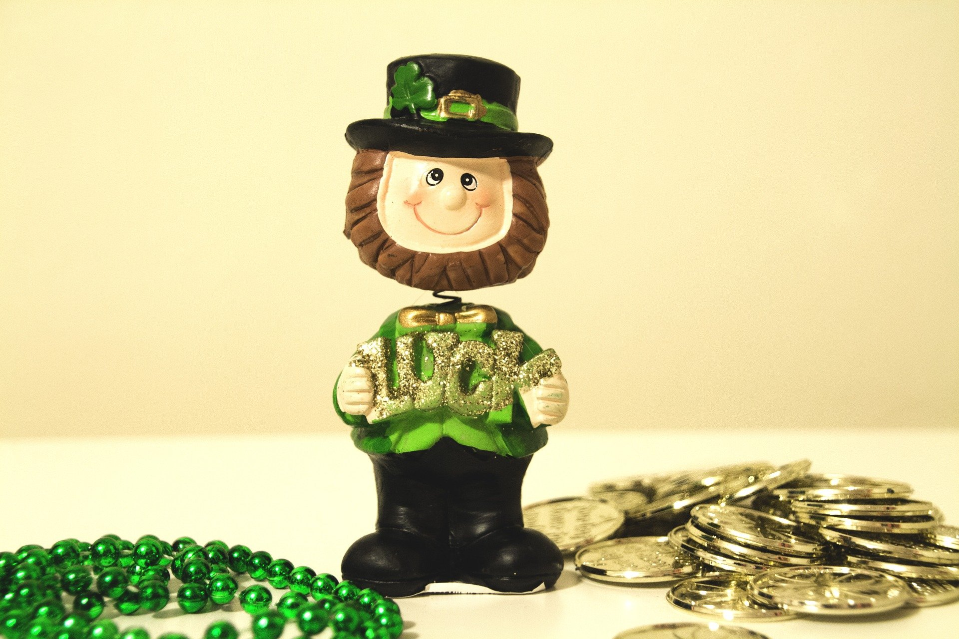 plastic toy leprechaun on a table next to a green bead necklace and gold coins