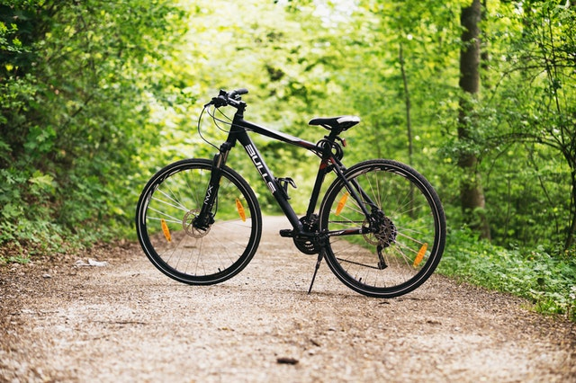 black bike bickycle on a dirt road in the middle of a forest