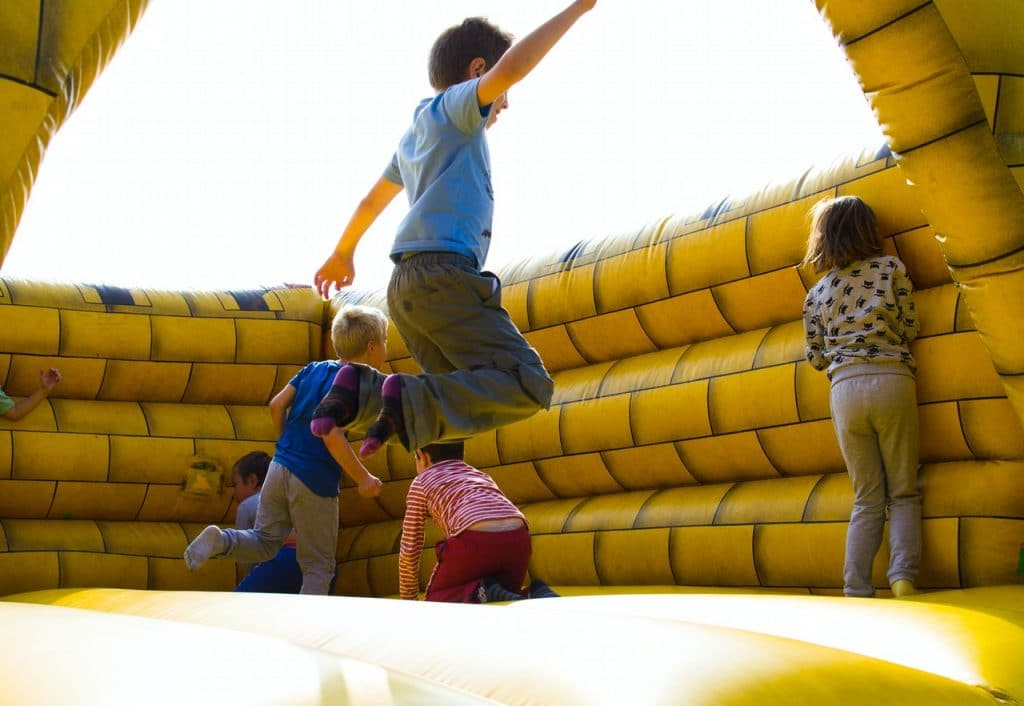 kids on a bounce house jumping outside