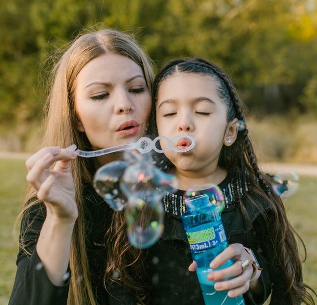 woman and her daughter blowing bubbles outside