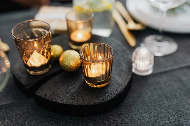 set of three candles lit on a black table around plate ware