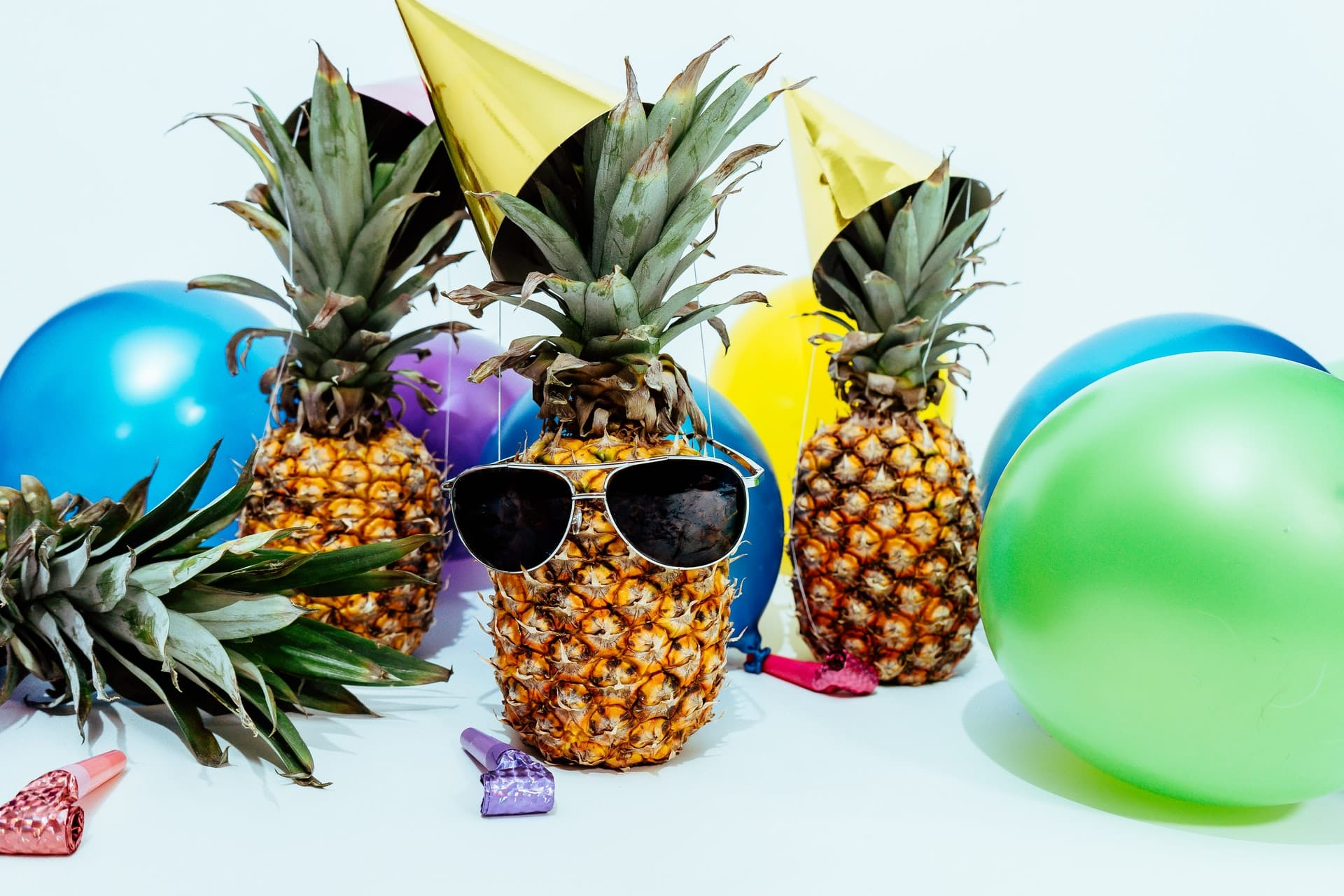 pineapples on a table with sunglasses and party hats surrounded by balloons and party favors
