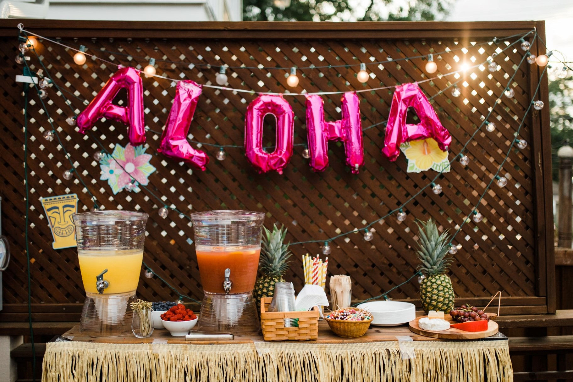 aloha party balloon outside over a party table with juices, drinks, food, and a luau theme