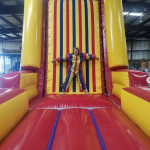 Velcro wall inflatable rental with woman stuck on the wall
