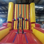 Velcro wall inflatable rental with woman standing on it with a jump suit