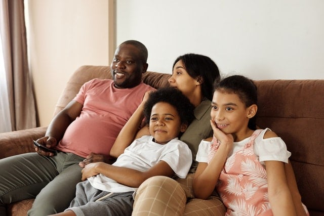 black family mom dad 2 kids sitting on the couch watching tv movie night
