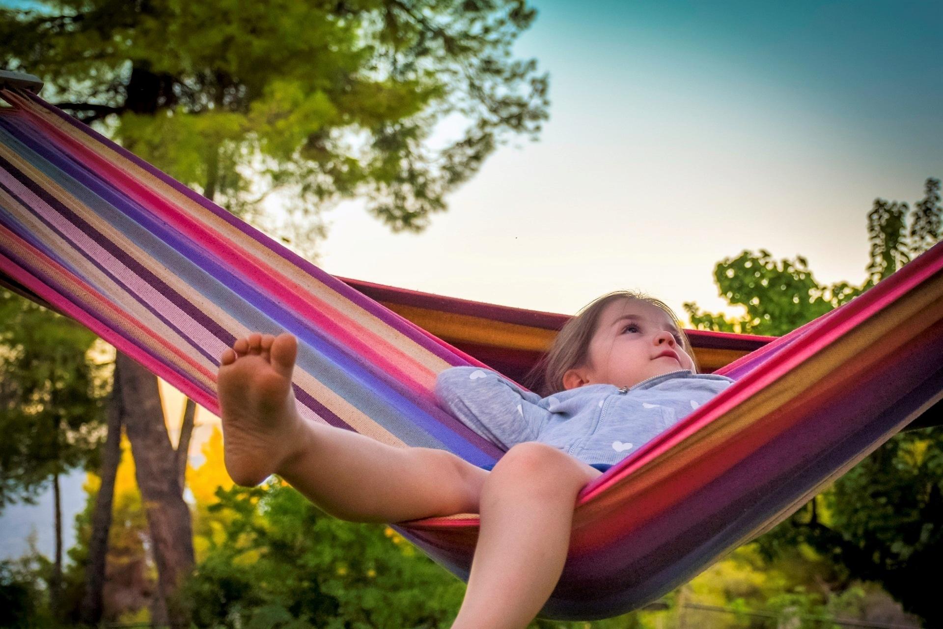 little kid sitting back on hammock outside in the backyard in summmer