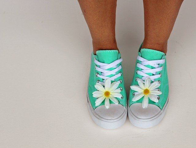 seafoam green shoes on a girl with white laces and white daisies on the toes