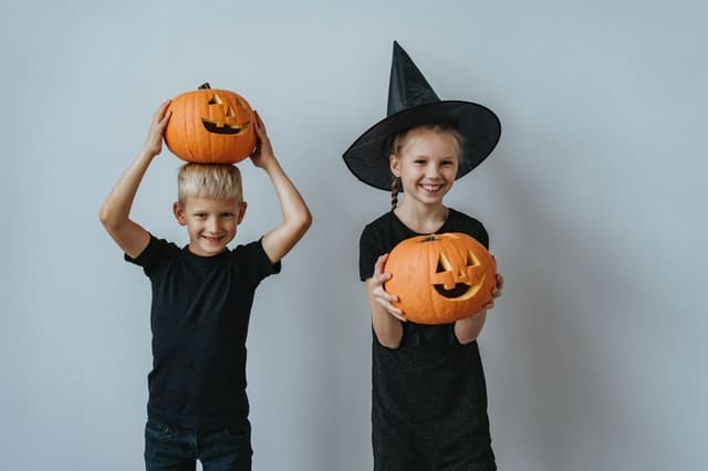 two kids dressed in black holding carved pumpkin jack-o-lanterns