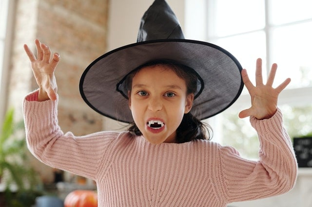 little girl dressed up for Halloween as a witch
