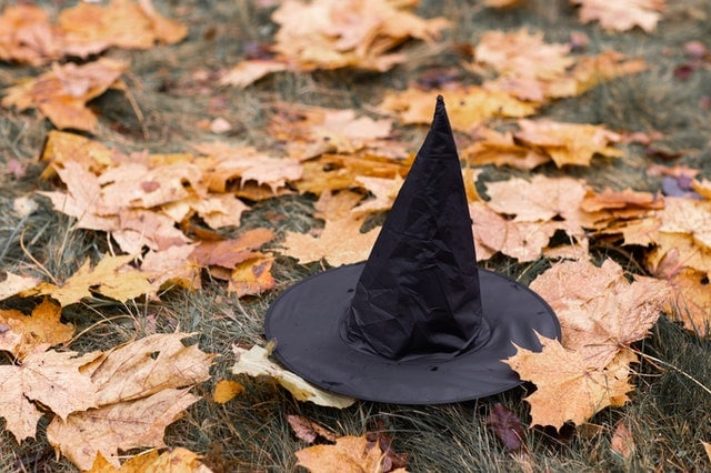 black witch hat on the ground surrounded by orange leaves