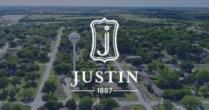 Justin, TX city logo over a picture of Justin, Texas